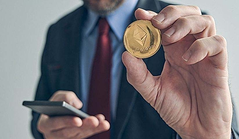 man holding ethereum coin
